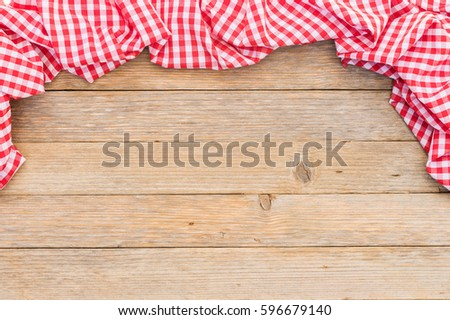 Shutterstock Red checked tablecloth frame on wooden table background.