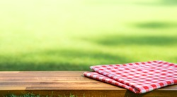 Red checked tablecloth on wood with blur green courtyard background.Summer and picnic concepts.Design for key visual food and drink products.no people