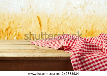 Red checked tablecloth on wooden deck table over wheat field background
