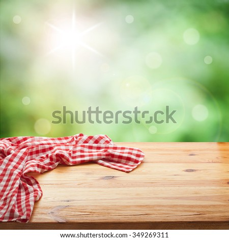 Red checked tablecloth on wooden deck table. Summer background. Mockup for design Stok fotoğraf ©
