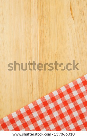 Red checked tablecloth on wooden table background