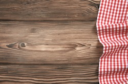 Red checkered kitchen cloth on dark wooden background,tabletop decorated with gingham picnic towel.Food design backdroop.