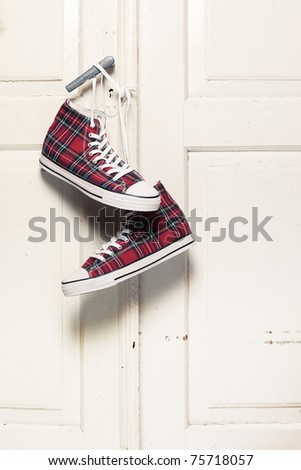 Red checkered sneakers hanging on door knob