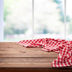 Red checkered tablecloth on empty wooden table near the window in kitchen. Napkin close up top view mock up for design. Kitchen rustic background.