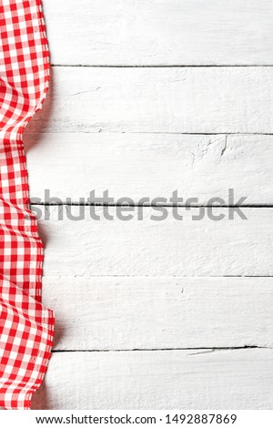 Red checkered tablecloth on white old wooden table with copyspace