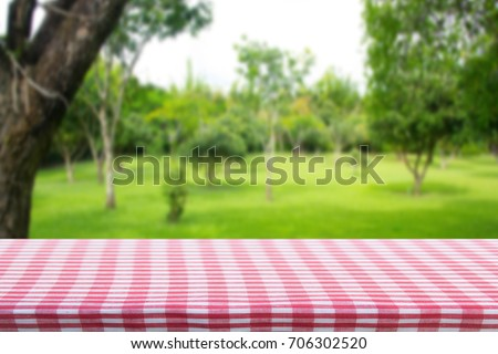 Red checkered tablecloth texture top view with abstract green bokeh from garden in morning background.For montage product display or design key visual layout and summer season. #706302520