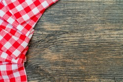 Red checkered towel on the kitchen table. Wooden kitchen table.