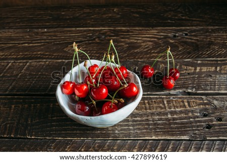 red cherries in a white ceramic bowl,  red cherries, red cherries on a brown background, bowl with cherries. #427899619