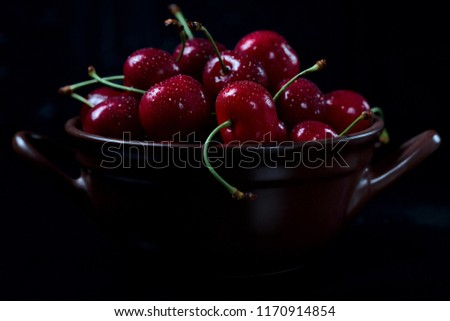 red cherries in ceramic bowl on dark background