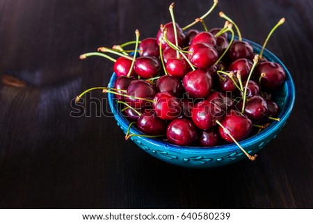 red cherries in green ceramic bowl on dark background #640580239