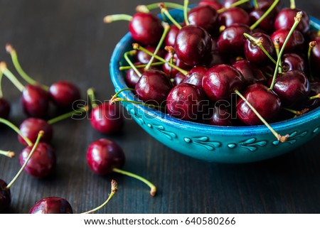 red cherries in green ceramic bowl on dark background #640580266