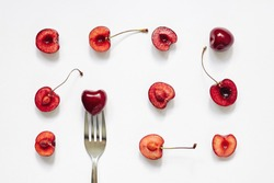Red cherry fruits and fork on white background. Summer, diet, healthy food eating consept. Top view, flat lay, layout, pattern