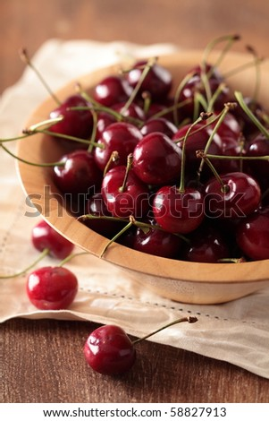 red cherry in a wood bowl