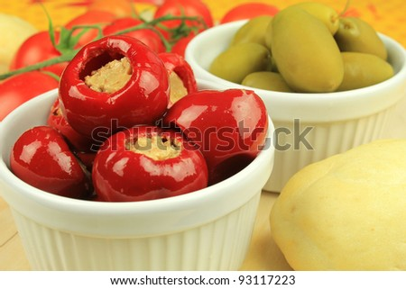 Red cherry pepper, or pimento, stuffed with tuna with green olives and tomatoes at the background