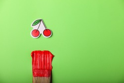 red cherry sticker, red paint and brush on a green background