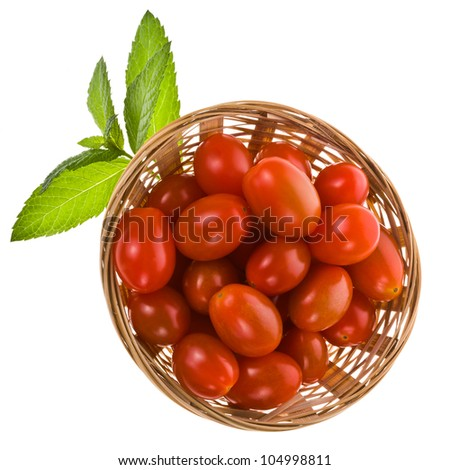 red cherry tomatoes in a wicker basket with green leaves isolated on white background