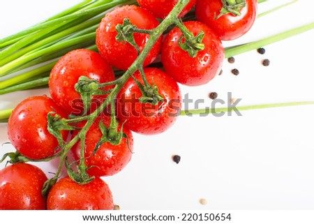 Red cherry tomatoes on a branch and green onion closeup on white background #220150654