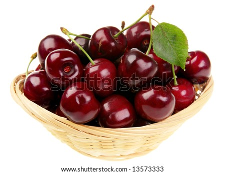 Red cherry with leaf in wood basket