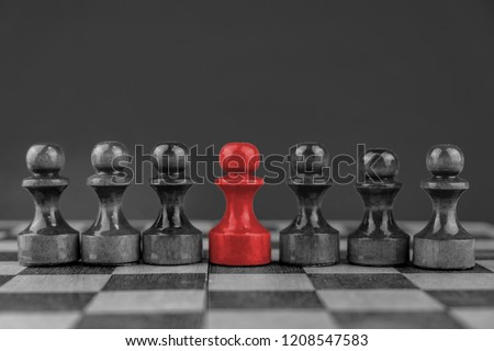 Red chess piece in a line with minor pieces. Concept of mobbing. bullying and individuality