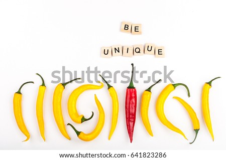 Red chili pepper standing out from crowd of identical yellow peppers on white background. Leadership, be unique, initiative, strategy, think different, business success concept