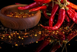 Red chili peppers and chili flakes spices and herbs on black background with reflection and copy space