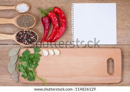 Red chili peppers, garlic, bay leaf, spices in spoon, notebook paper and kitchen board on oak wood texture background - stock photo