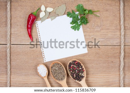 Red chili peppers, garlic, bay leaf, spices in spoons, notebook paper on oak wood texture background