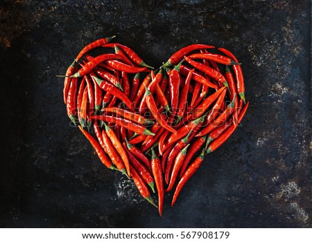 Shutterstock Red chili peppers in heart shape, for valentine's day on old black metal background.