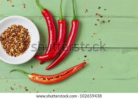Red chili peppers on an old green board