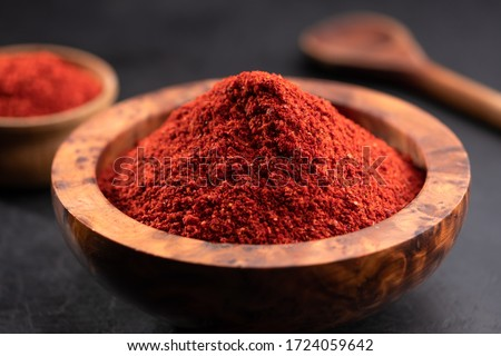 Red chili powder or paprika in a wooden bowl on a dark background, close-up. Cooking ingredients, flavor. Stockfoto ©