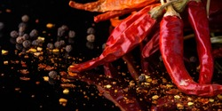 Red chilli pepper and flakes on a black banner background with reflection and copy space