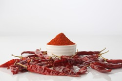 red chillies with red chilly powder on white background.
