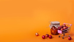 Red chinese cherry apples in small shopping cart and canning jar of apple jam on orange background with copy space. Horizontal banner with ripe fruit concept. Fermented fruits.