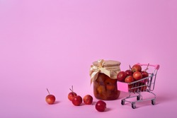 Red chinese cherry apples in small shopping cart and canning jar of apple jam on pink background with copy space. Horizontal banner with ripe fruit concept. Fermented fruits.