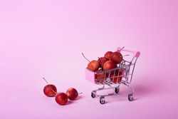 Red chinese cherry apples in small shopping cart on pink background with copy space. Ripe fruit concept. Healthy still life
