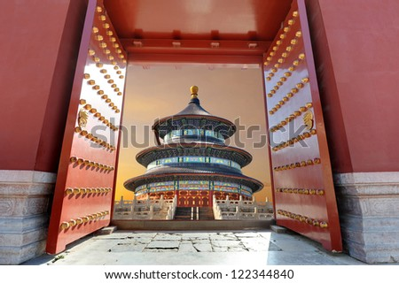 Red Chinese gate opening to a Chinese building in sunset light ( Temple of Heaven or Tiantan Temple in Beijing - China )