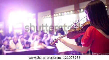 Red Chinese girl playing violin in the super market for x'mas holiday