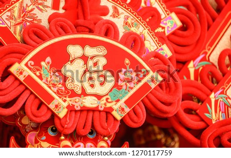 "Red Chinese knotting with and chinese character on it which means ""good luck"" or ""blessing""."