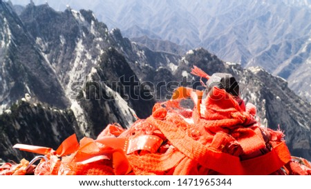 Red chinese ribbons placed on the top of North Peak - one of five main peaks belonging to sacred taoist mountain Mount Huashan, popular touristic place, China