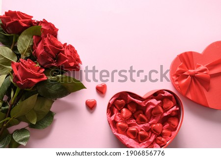 Red chocolate sweets and roses on pink for Valentine's day. Greeting card with copy space. Stock photo ©