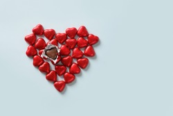 Red chocolate sweets as heart on blue background. Valentine's day concept.