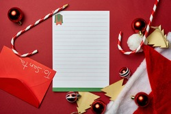 red christmas background to put texts Christmas pencil on white sheet, red envelope, Santaclaus hat, wooden tree-shaped decorations, and red and white Christmas balls with candy canes