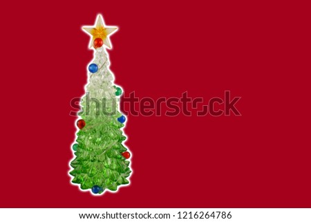 Red christmas background with a tree stock images. Simple Christmas card. Christmas decoration on a red background. Christmas tree with a star. Holiday background with copy space for text
