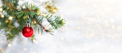 Red Christmas ball hangs on a snow-covered branch of a Christmas tree against a festive background of white snow and golden bokeh lights with copy space. New Year, greeting and holiday card, banner.