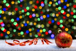 Red Christmas ball isolated on colorful lights background.