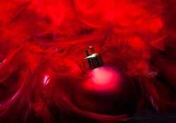Red Christmas ball lying on wooden floor near red feathers