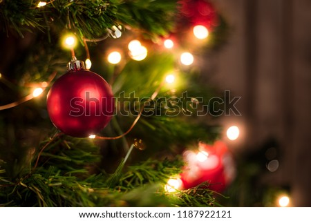 Red Christmas ball on a Christmas tree with a garland on the background of a wooden wall #1187922121