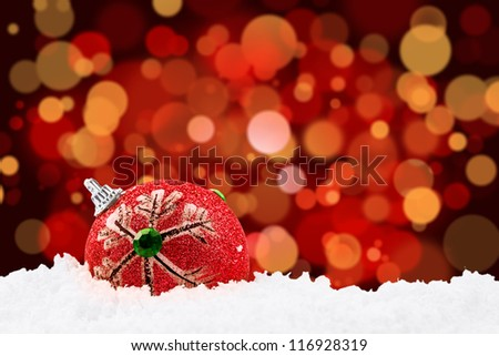 Red christmas ball on the snow with red christmas defocused light background