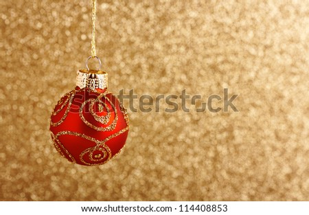 Red Christmas ball over glittering golden background