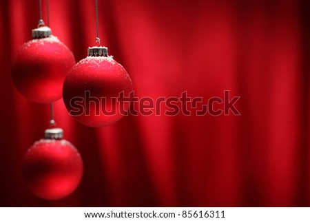 Red Christmas balls hanging over red background.